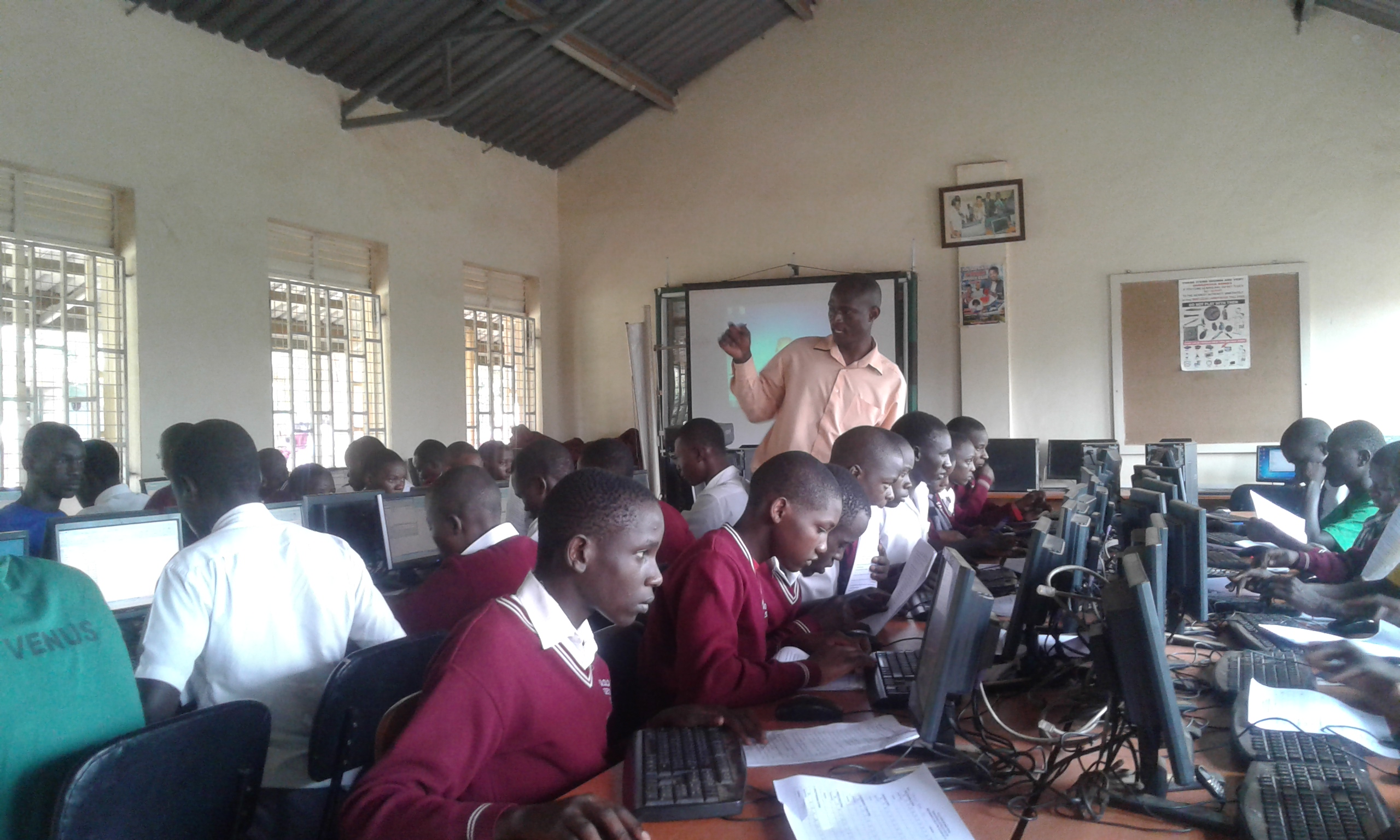 Mr. Mukalele Rogers, a Teacher at Kololo Senior Secondary School, Kampala, guiding Students using computers in a computer Lab. Digital Education is on the rise in Uganda
